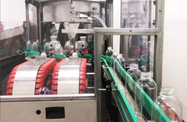 Botellas vacías entrando en la máquina posicionadora y enjuagadora | Traktech SL